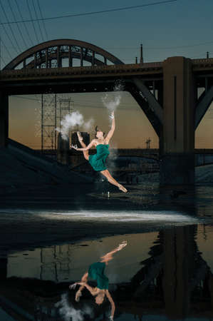 entertaining area: Female ballet dancer leaping whilst releasing powder explosion above river at sunset, Los Angeles, USA