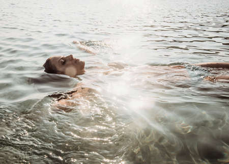 Beautiful young woman floating in sunlit sea