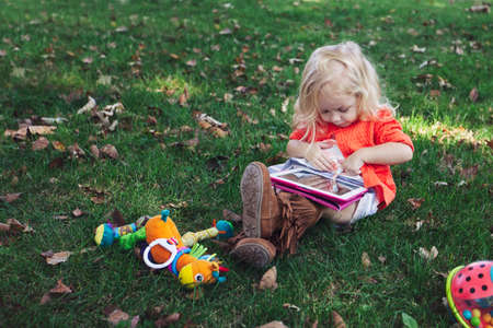 Girl sitting on grass with toys looking down using digital tablet