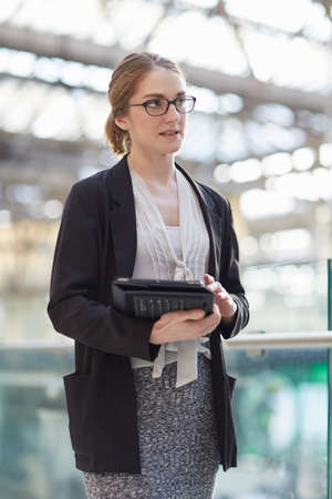 Businesswoman wearing eye glasses holding digital tablet looking away
