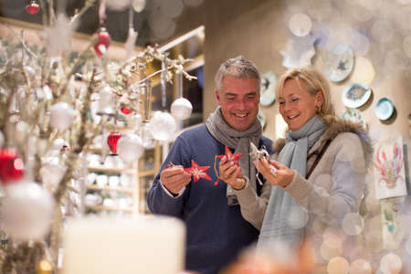 Mature couple choosing star decorations in gift shop, Majorca, Spain