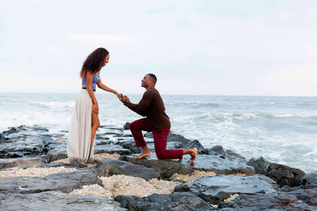 Mid adult man kneeling on rocks beside sea, proposing to young woman