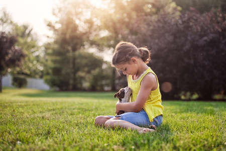admired: Girl sitting on grass holding Boston Terrier puppy