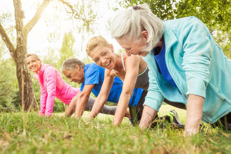 athletic wear: Group of adults exercising, doing push ups, outdoors LANG_EVOIMAGES