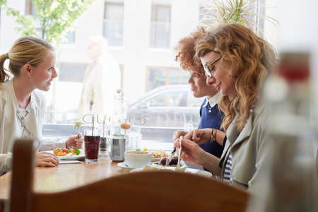 Three female friends eating lunch in cafe LANG_EVOIMAGES