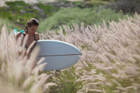 Young woman walking through tall grass carrying surfboard looking down LANG_EVOIMAGES