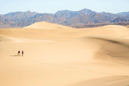 Two people walking across sand, Death Valley, California, USA