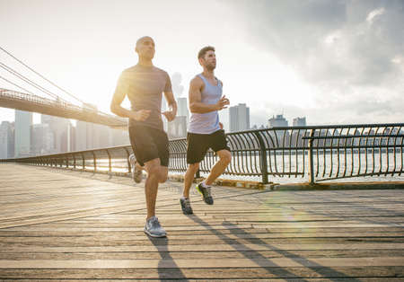 Two male running friends running in front of Brooklyn bridge, New York, USA
