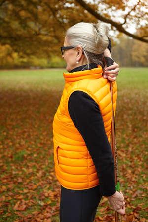 Senior female nordic walker exercising with walking poles in park