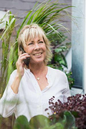 Portrait of mature woman in garden, using smartphone
