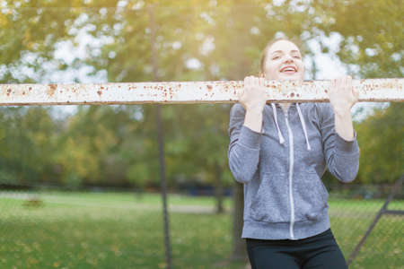 Young woman doing chin up on goal post looking at camera smiling