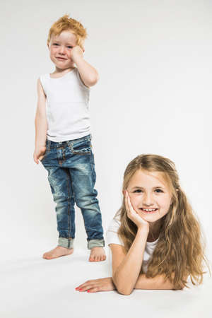 Studio portrait of happy girl lying on front whilst her brother is crying