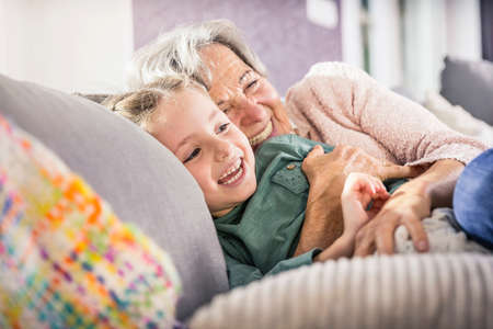 Senior woman and granddaughter cuddling on sofa