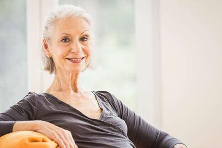 Portrait of happy senior woman on living room sofa