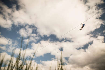 Mature man on zip wire over field LANG_EVOIMAGES