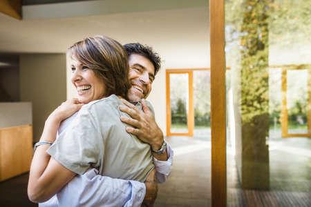 Mature couple hugging outside new house