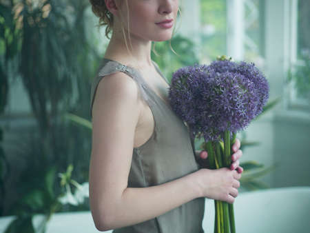 vintage: Young woman holding bouquet of flowers, mid section