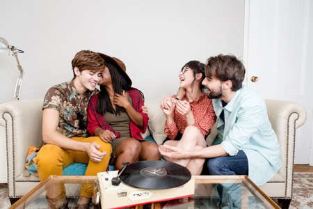 Young hipster couples laughing whilst listening to vinyl music in apartment LANG_EVOIMAGES