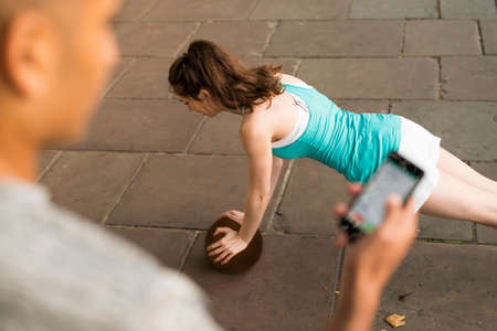 Over shoulder view of trainer timing female runners push ups on smartphone