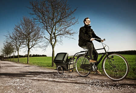 Man riding bicycle with carriage on country road, Ringsted, Denmark LANG_EVOIMAGES