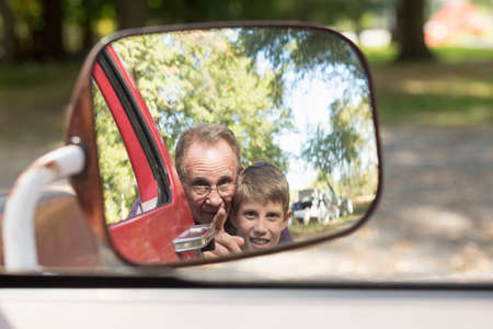 Senior man and grandson reflected in truck wing mirror