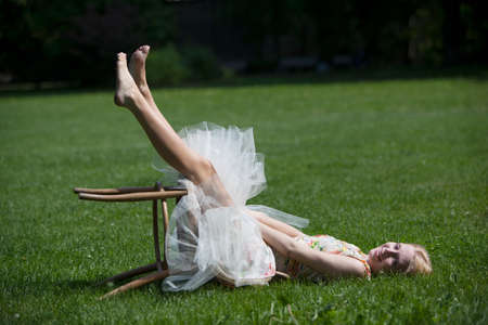 Portrait of young woman lying on grass, sitting on fallen stool, smiling LANG_EVOIMAGES