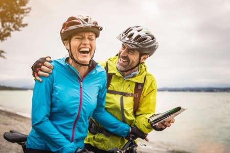 Mature mountain biking couple laughing whilst checking map at lakeside