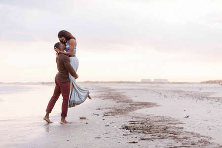 arms lifted up: Couple of beach, hugging, face to face, man lifting woman