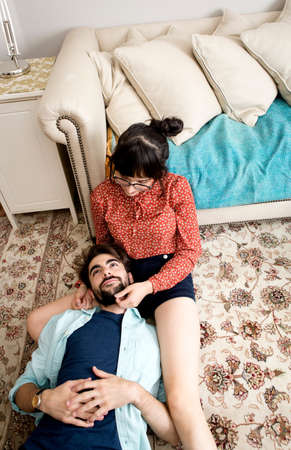 above 18: Overhead view of young hipster couple sitting on rug in  apartment LANG_EVOIMAGES