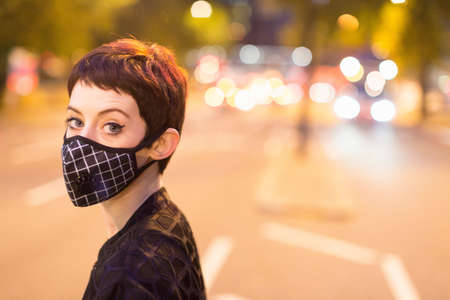 Head and shoulders of young woman wearing face mask looking at camera, eyebrow raised LANG_EVOIMAGES