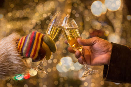 Close up of couples hands making a champagne toast in front of xmas lights LANG_EVOIMAGES