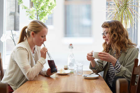 Two female friends drinking and chatting in cafe