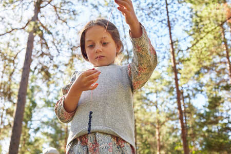 Girl dressed in retro clothing threading berries in forest