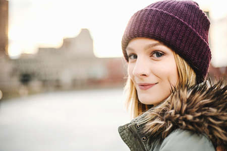 purples: Portrait of young woman wearing knitted hat and fur hood