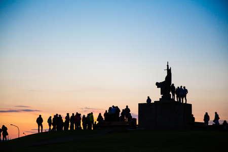 Silueta de multitud de personas alrededor del monumento al atardecer, Reykjavik, Islandia