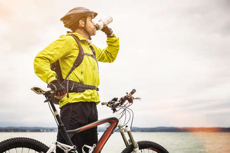 Mature male mountain biker drinking water at lakeside LANG_EVOIMAGES
