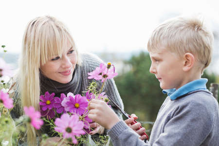 Mother and son cutting organic flowers in garden LANG_EVOIMAGES