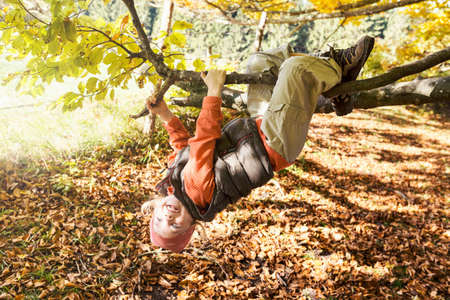 trouble free: Girl hanging upside down on tree looking at camera smiling LANG_EVOIMAGES