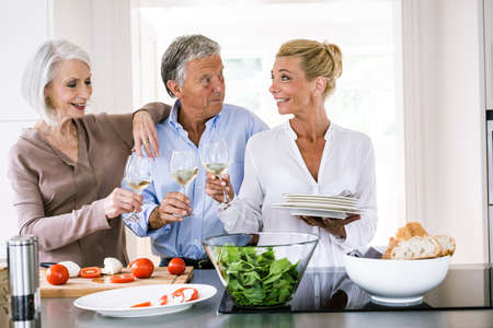 housing lot: Happy senior couple and mature woman raising a glass of wine to each other in kitchen