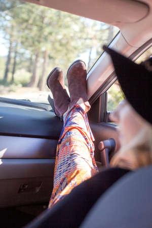 getting out: Over the shoulder view of young woman wearing hat sitting in car, legs raised on dashboard
