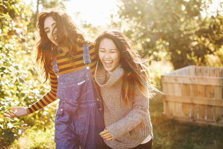Two young women, in rural environment, laughing