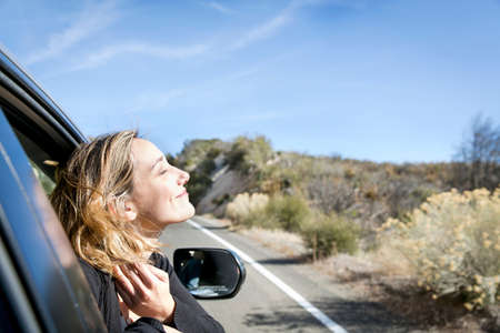 Side view of young woman poking head out of car window eyes closed smiling