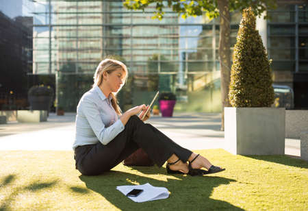 desk clerk: Young businesswoman sitting outside city office using digital tablet