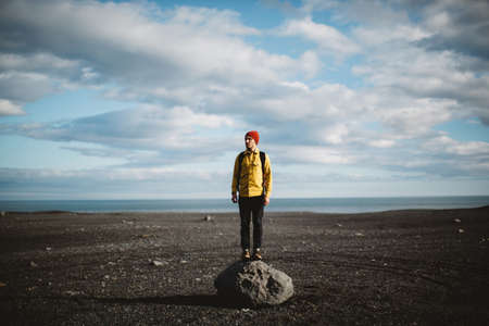 tranquillity: Mid adult man standing on top of boulder on volcanic landscape looking away, Iceland LANG_EVOIMAGES