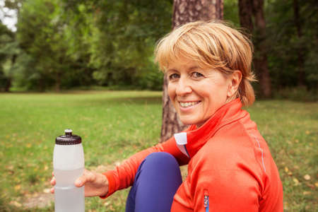 Portrait of mature woman, outdoors, holding water bottle LANG_EVOIMAGES