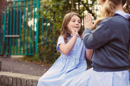 Elementary schoolgirls playing hand clapping game in school playground