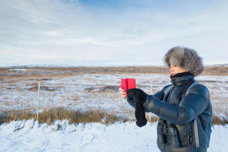 Mature woman taking photograph on snow-covered field, Iceland LANG_EVOIMAGES