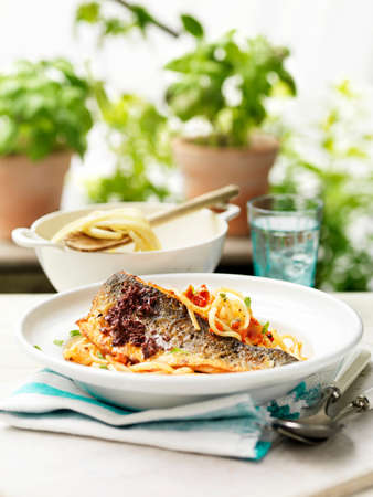 Bowl of fish kebab with spaghetti and tomato chilli on garden table LANG_EVOIMAGES