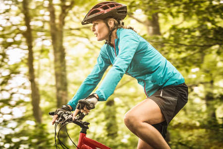 Happy mature female mountain biker speed cycling in forest