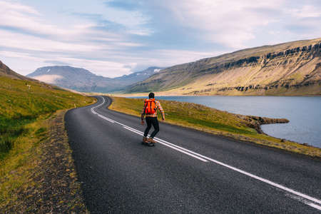 Rear view of mid adult man skateboarding on curving open road by lake, Iceland